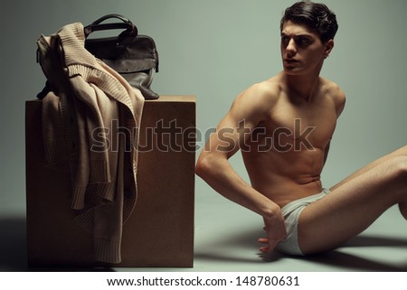 Male high fashion concept. Portrait of a handsome male model sitting near a wooden cube in trendy underwear. Cardigan and leather bag on a cube. Perfect skin & haircut. Vogue style. Studio shot