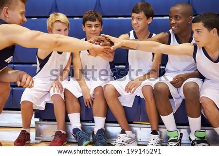 Male High School Basketball Team Having Team Talk With Coach - stock photo
