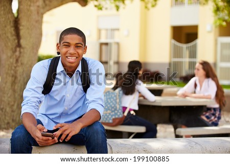 Male High School Student Using Phone On School Campus - stock photo