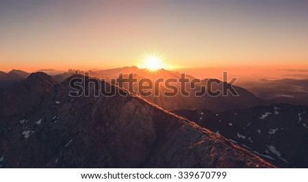 Male hiker at the top of the mountain at sunrise. Beautiful scenery in the Alps in the morning.