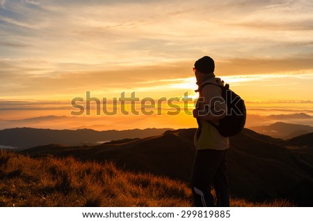 Male hiker climbing to the peak at dawn.