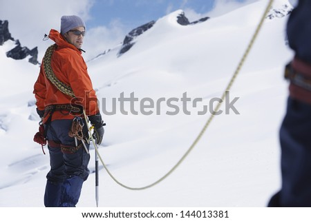 Male hiker connected to safety line in snowy mountains