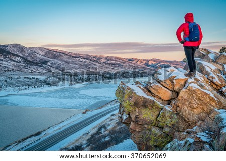 male hiker contemplating winter sunrise over frozen Horsetooth Reservoir  at Rocky Mountains foothills near Fort Collins, Colorado - stock photo