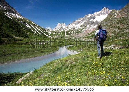 Male hiker enjoying the view over the beautiful landscape of Lac Combal, Val Veny, Courmayeur, Italy - stock photo