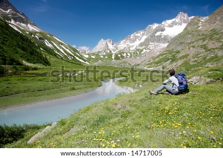 Male hiker enjoying the view over the beautiful landscape of Lac Combal, Val Veny, Courmayeur, Italy