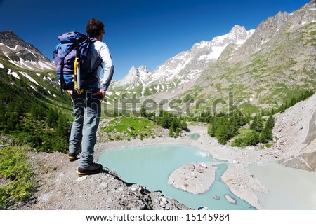 Male hiker enjoying the view over the beautiful landscape of Miage Lake, Mont Blanc, Courmayeur, Italy