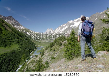 Male hiker enjoying the view over the beautiful landscape of Mige Lake, Mont Blanc, Courmayeur, Italy