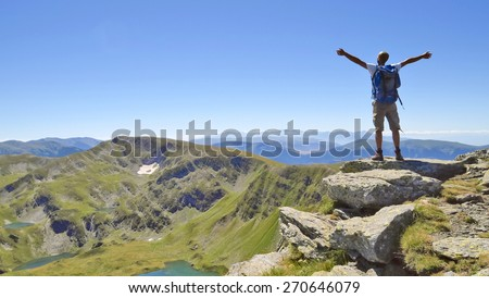 Male hiker in Rila mountains, Bulgaria, with arms stretched out to enjoy the mountain scenery - stock photo