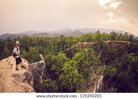 Male hiker in white shirt and backpack looking at view from  canyon edge - stock photo