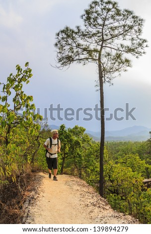 Male hiker in white shirt and backpack walking along mountain trail in Pai Canyon, Thailand - stock photo