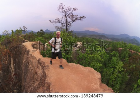 Male hiker in white shirt and backpack walking along narrow mountain path in red canyon - stock photo