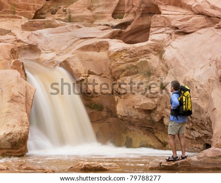 Male hiker looking at beautiful waterfall flowing from red rocks.