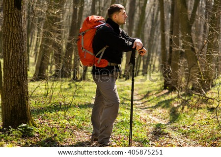 Male hiker looking to the side walking in forest