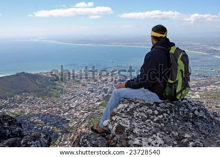Male hiker sitting on rock above Cape Town South Africa - stock photo