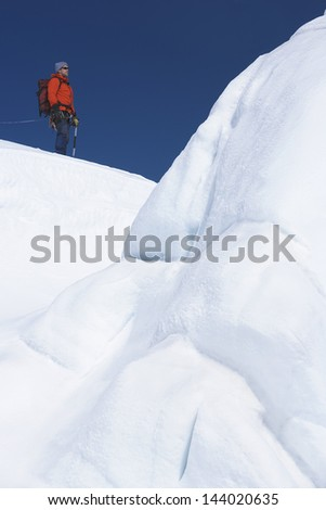 Male hiker standing by ice formation in snowy mountains