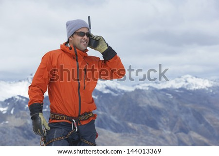 Male hiker using walkie talkie against mountain peaks - stock photo