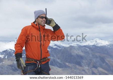 Male hiker using walkie talkie against mountain peaks - stock photo