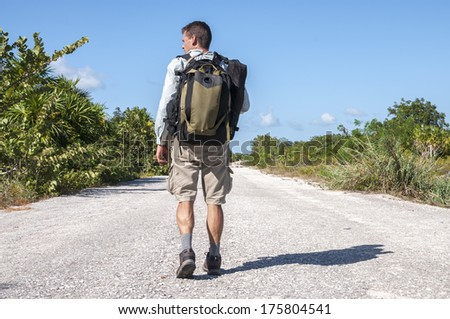 Male hiker with backpack and gear walking alone down lonely asphalt road flanked by tropical vegetation - stock photo