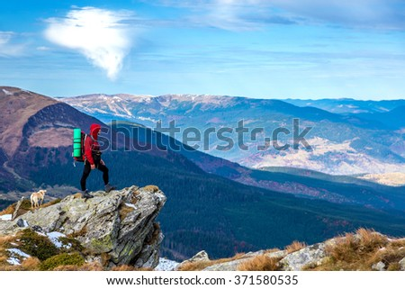 Male Hiker with Backpack and Mat staying on sharp rocky Cliff and observing Mountains Panoramic View