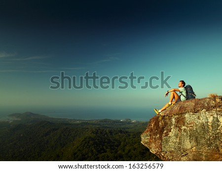 Male hiker with backpack relaxing on top of a mountain - stock photo