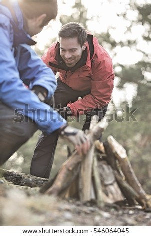 Male hikers lighting bonfire in forest