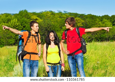 Male hikers showing opposite directions - stock photo