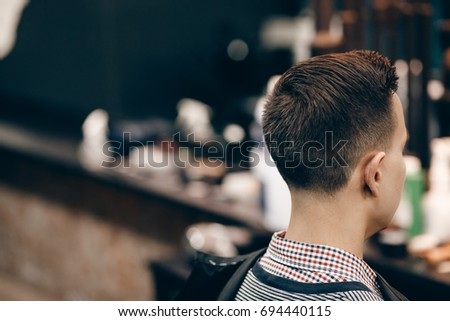 Male hippy customer in barber shop hairdresser on fashionable haircut, rear view. They cut her hair, put her hair dryer and wax. Concept of hair care. Toned photo.