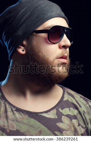 Male hipster with beard and sun glasses against black background