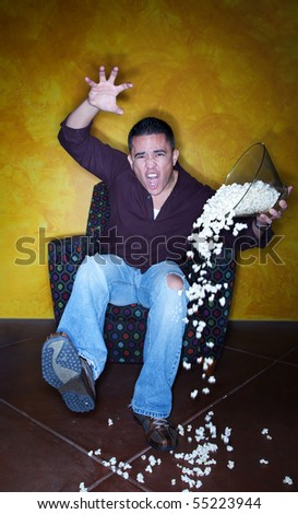 Male Hispanic sports fan with popcorn watching television - stock photo