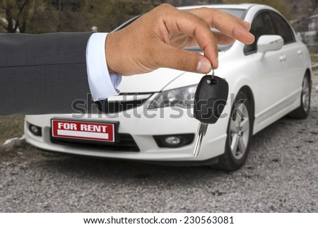 Male holding car keys with a rental car on background - stock photo