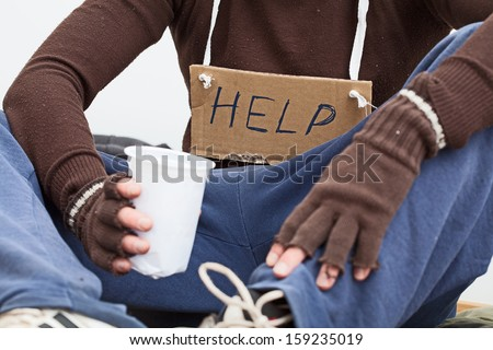 Male homeless sitting on a street with sign asking for help - stock photo