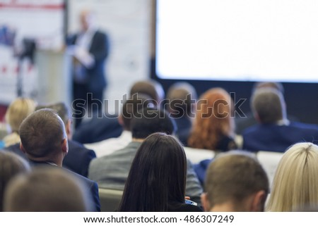 Male Host Presenting Report During the Conference. Speaking in Front of Large Group of People. Horizontal Image Composition