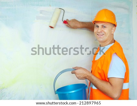 male house painters with paint rollers in new house - stock photo