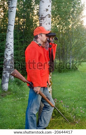 male hunter holding his rifle and looking through binoculars - stock photo