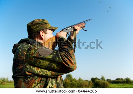 Male hunter in camouflage clothes on the field aiming and shooting with hunting rifle to gamebird during a hunt - stock photo