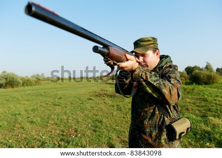 Male hunter in camouflage clothes on the field aiming the hunting rifle during a hunt - stock photo