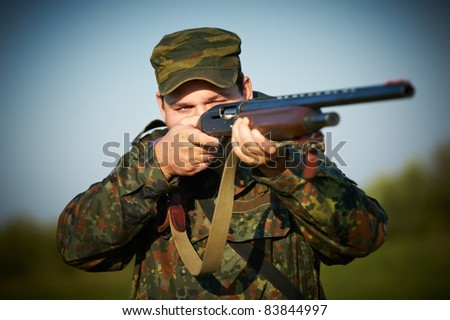 Male hunter in camouflage clothes on the field aiming the hunting rifle during a hunt. - stock photo