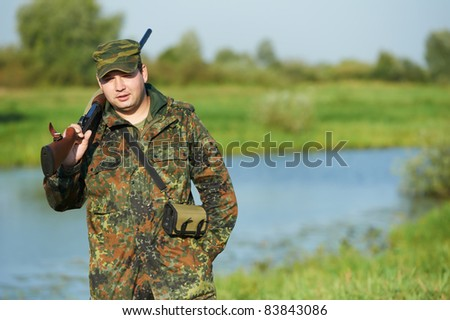 Male hunter in camouflage clothes ready to hunt at lake bank with hunting rifle