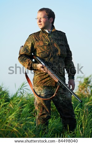 Male hunter in camouflage clothes ready to hunt at lake bank with hunting rifle - stock photo