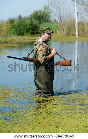 Male hunter in camouflage clothes standing at water bog with hunting rifle during a hunt