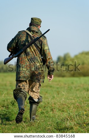 Male hunter in camouflage clothes walking on the field with hunting rifle during a hunt