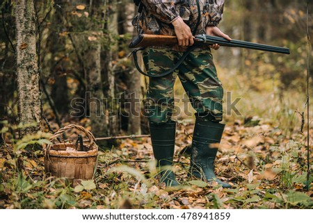 Male hunter in the autumn forest. A man holding a gun.