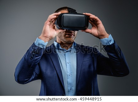 Male in a suit with virtual reality glasses on his head. Isolated on grey background.