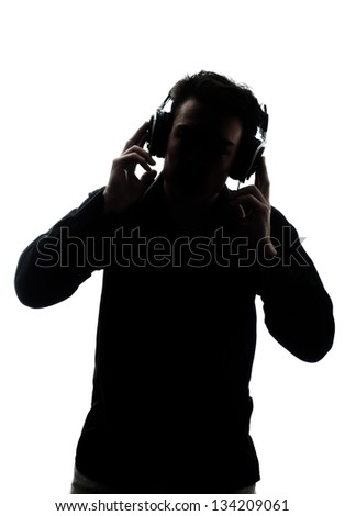 Male in silhouette listening to headphones isolated on white background - stock photo