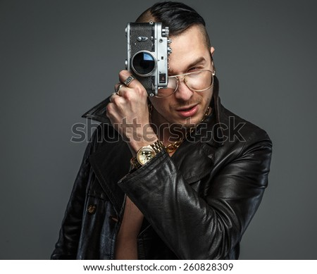 Male in skin coat holds photo camera. - stock photo