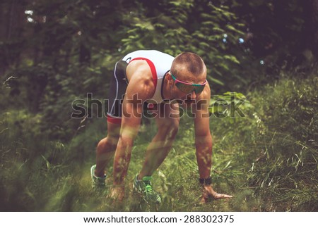 Male in sportswear and sunglasses running in the forest. - stock photo