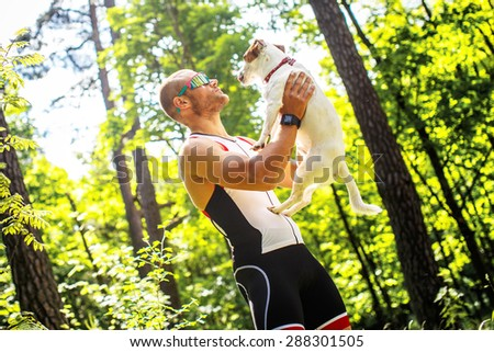 Male in sportswear holding dog in his hands. - stock photo