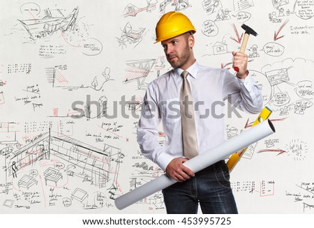 Male in white shirtl and hard cap holding drawning tube and working level over desk with drawnings.