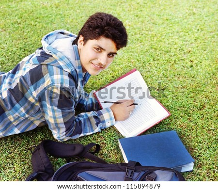 Male Indian / Asian college student lying / studying over the grass. - stock photo