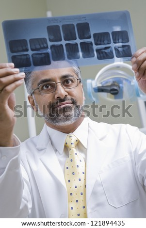 Male indian dentist examining x-ray report in clinic - stock photo